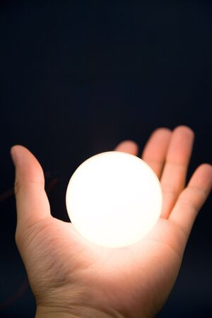 Hand holding a bright ball, Concept of magic Stock Photo - 5173268