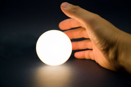 Hand touching a bright ball, Concept of magic Stock Photo - 5200317