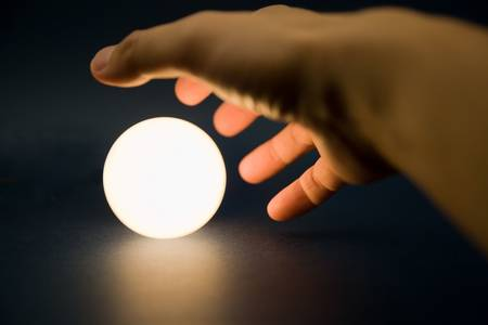 Hand touching a bright ball, Concept of magic photo