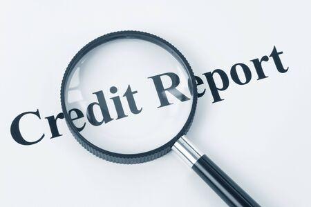 Informe de crédito y una lupa Foto de archivo - 5463249
