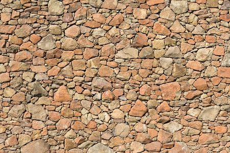 stone wall: Yellow rock wall pattern for background Stock Photo