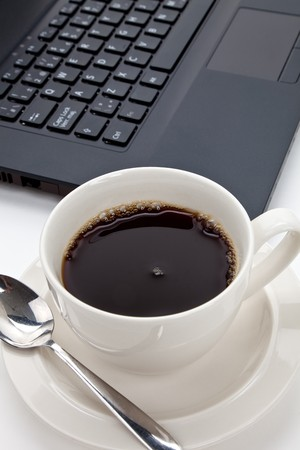 Coffee cup and computer close up