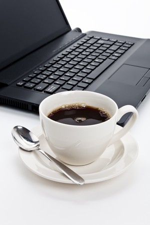Coffee cup and computer close up photo
