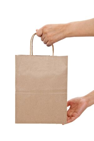 carrying: Brown paper shopping bag with white background