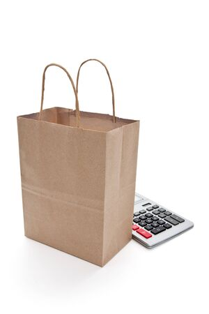 Brown paper shopping bag and calculator with white background