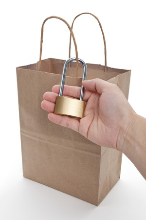 Brown paper shopping bag and lock, concept of tighten tudget