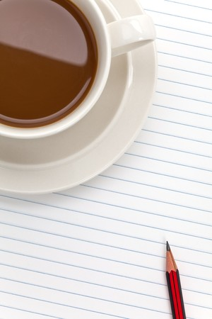 Coffee cup and note pad close up