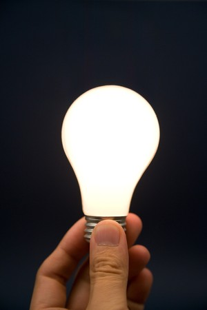 hand: Hand holding a Bright Light Bulb, Concept of Inspiration, Ideas Stock Photo
