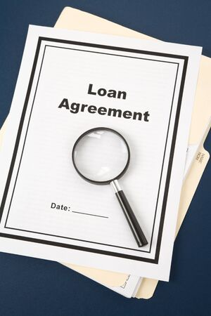 Loan Agreement and Magnifying Glass, business concept photo
