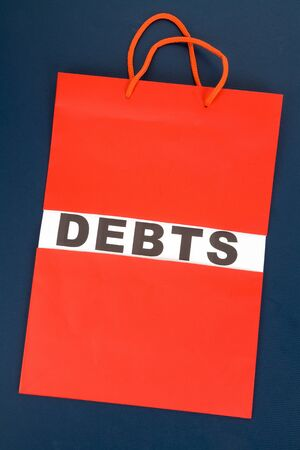 consumerism: Shopping Bag and word debts concept of Financial difficulty