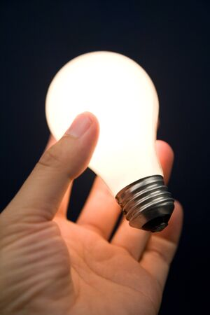 creative: Hand holding a Bright Light Bulb, Concept of Inspiration, Ideas Stock Photo