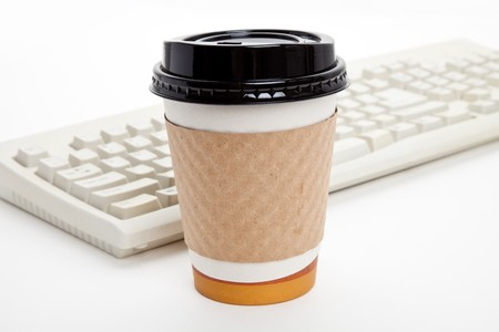 Disposable Coffee Cup and Computer Keyboard with white background Stock fotó