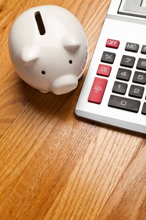 White Piggy Bank and calculator on wood table top photo