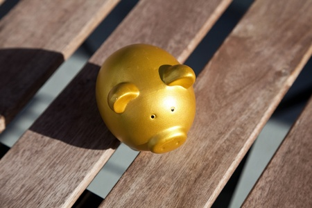 table top: Gold Piggy Bank on wood table top Stock Photo