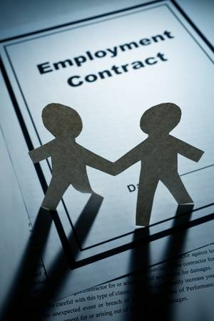 Employment Contract and Paper Chain Men close up photo