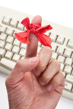 reminding: Red bow on finger and computer keyboard