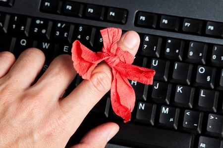 Red bow on finger and computer keyboard photo