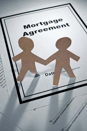 Mortgage Agreement and Paper Chain Men close up Stock Photo - 10171874