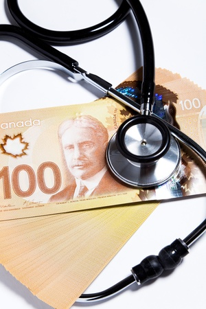 canadian currency: Stethoscope and Canadian dollar, concept of Financial Health