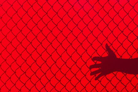 background texture: Red Fence and hand Shadow, concept of freedom