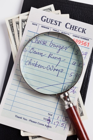 Guest Check and magnifying glass, concept of restaurant expense fraud. photo