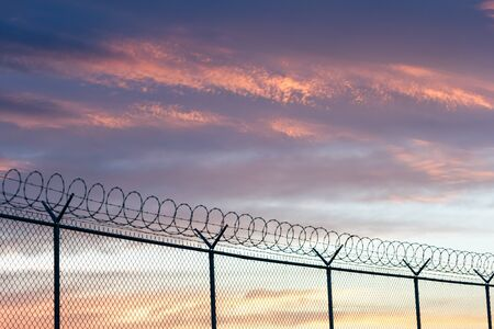 barbed wire fence: barbed wire fence and sky Stock Photo