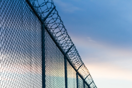 mesh fence: barbed wire fence and sky Stock Photo
