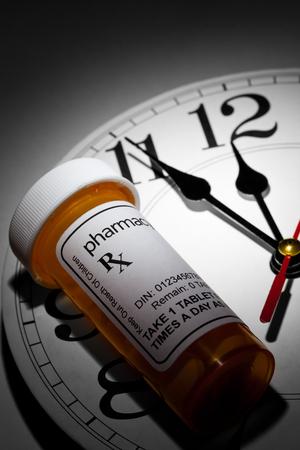 Klok en pillenfles, concept voor gezondheidszorg en geneeskunde Stockfoto
