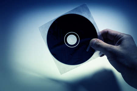 rom: Hand holding a CD, DVD disc Stock Photo