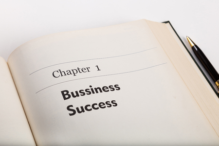 chapter one, in an open book with a pen, business success