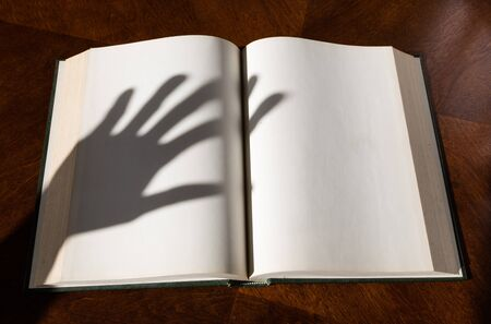 hardcover book: Blank white pages in an open hardcover book and hand shadow