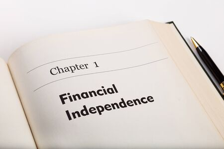 one sheet: chapter one,  in an open book with a pen, financial  independence, fake book.