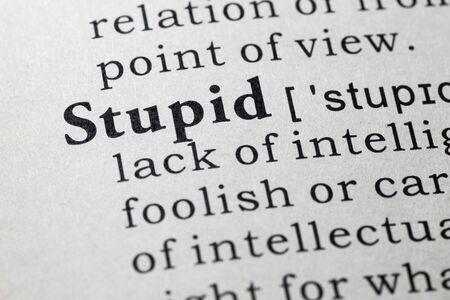 Fake woordenboek, woordenboek definitie van het woord dom. Stockfoto