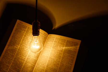 electric bulb: electric bulb illuminating a book