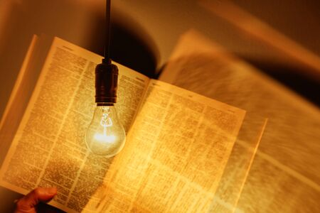 electric bulb illuminating a book
