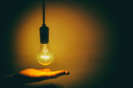 light bulb and hand with dark background Stock Photo