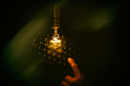 Light bulb and computer keyboard, concept of wisdom. Stock Photo