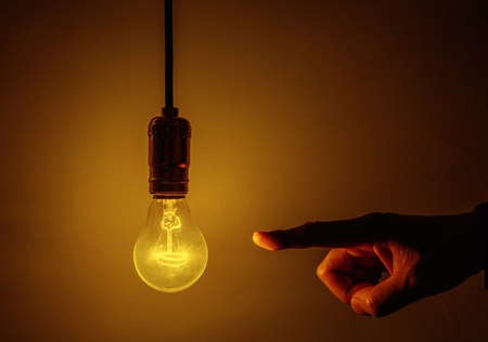 creativity and innovation: light bulb and hand with dark background Stock Photo