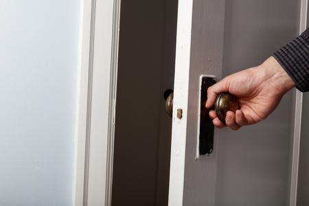 old wooden door with door knob, close up.