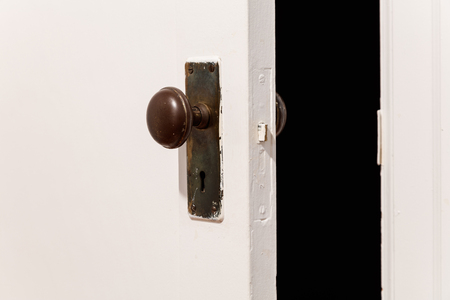 door knob: old wooden door with door knob, close up.