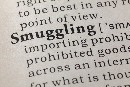 Fake Dictionary, Dictionary definition of the word smuggling. including key descriptive words. Stock Photo