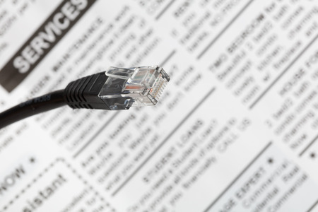 Black network cable plug with newspaper , close up view.