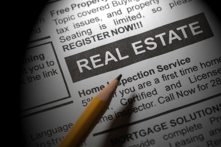 Fake newspaper, newspaper headline real estate and pencil