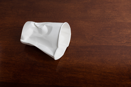 Crumbled White paper coffee cup on table.