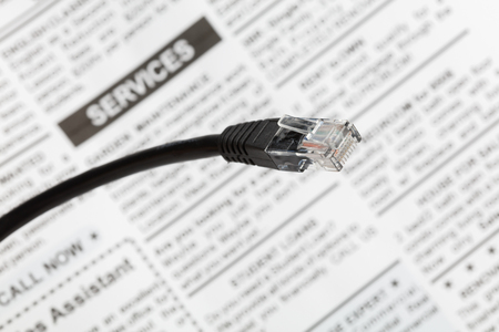 Black network cable plug with fake newspaper , close up view. Stockfoto