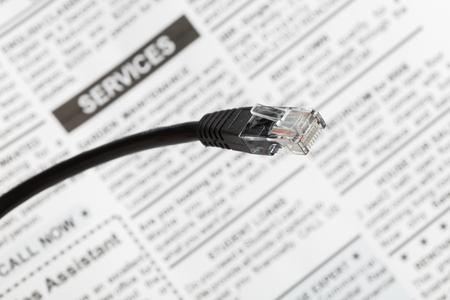 Enchufe de cable de red negro con periódico falso, vista cercana. Foto de archivo