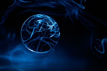 Transparent Crystal ball on black with blue light, close up. Imagens - 121474182