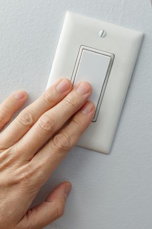 hand turning white light switch on or off Standard-Bild - 117642304