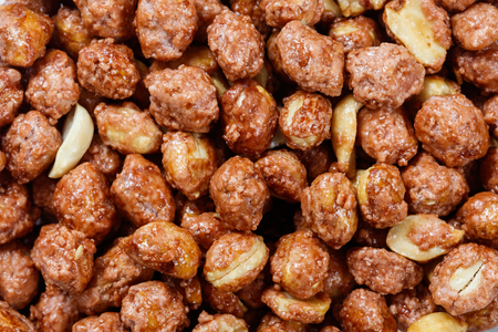 Roasted peanuts in icing sugar close up.