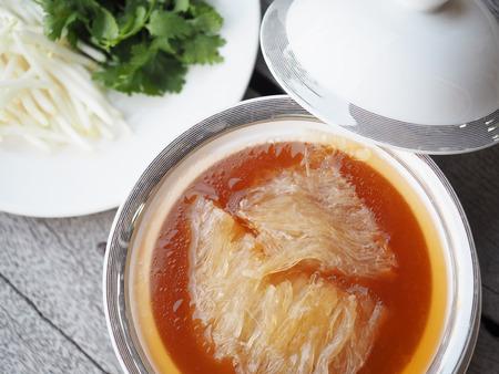 La soupe de nageoire de requin chinois avec la sauce brune servent dans le bol royal blanc - argenté, la décoration avec les germes de soja et la coriandre, sur le fond en bois gris. Banque d'images